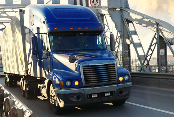 Blue semi truck transporting along a bridge